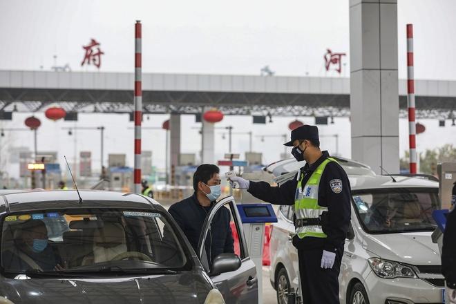 Cảnh sát kiểm tra nhiệt độ tài xế ôtô trên cao tốc ở Vũ Hán, tỉnh Hồ Bắc, ngày 24/1. Ảnh: AFP.