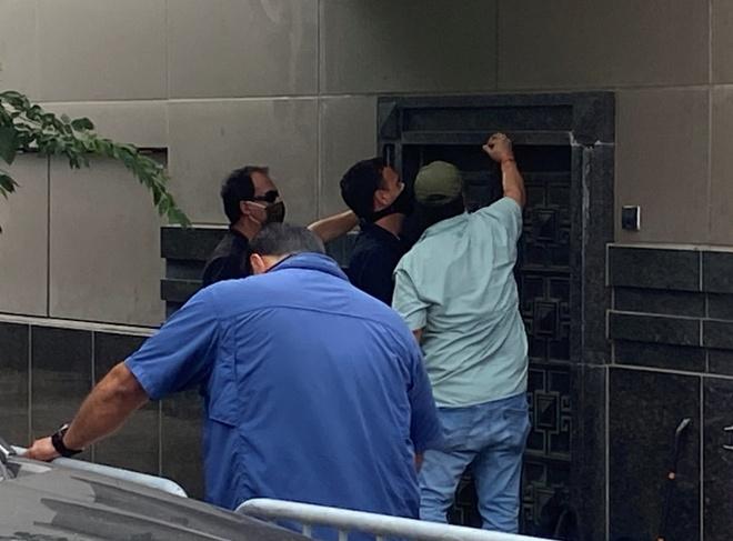 Một nhóm người dùng dụng cụ cố mở một cánh cửa ở phía sau lãnh sự quán ở Houston. Ảnh: Reuters.