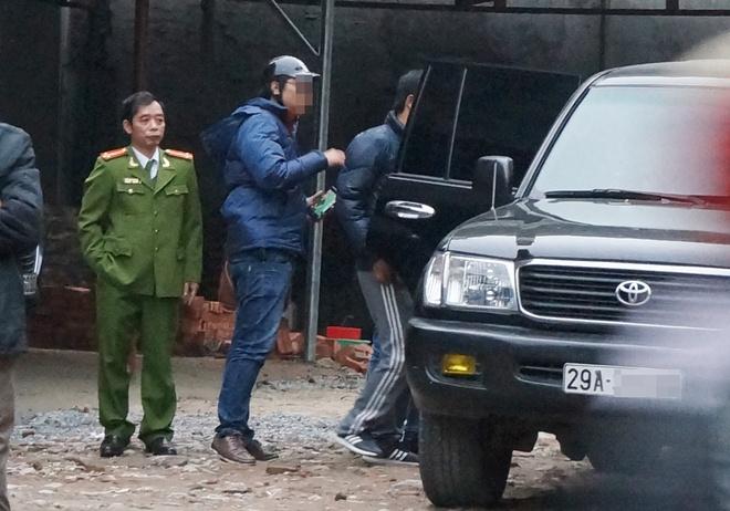 Canh sat mac ao giap, mang sung kham nha nghi pham danh bac hinh anh 2 Cảnh sát đưa người liên quan lên xe ôtô. Ảnh: Việt Đức.