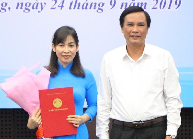 Ông Trần Văn Miên trao quyết định và tặng hoa cho bà Hạnh. Ảnh: Nguyên Vũ.