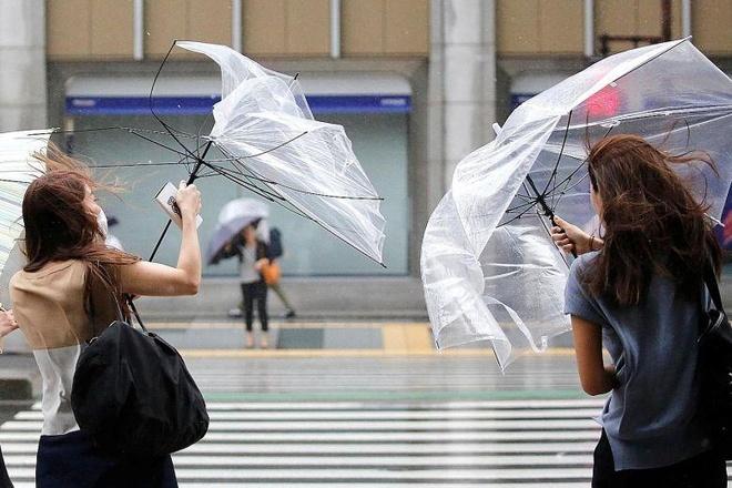 Người qua đường dùng ô trong một cơn bão ở Tokyo tháng 8/2018. Ảnh: Reuters.