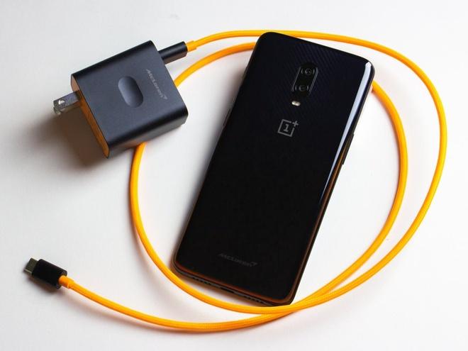 Sạc và dây của OnePlus 6T McLaren Edition. Đây là cục sạc nhanh, với công nghệ đặc biệt giúp điện thoại không nóng khi sạc. Sợi dây sạc còn được bọc dù với màu da cam rất lạ mắt.