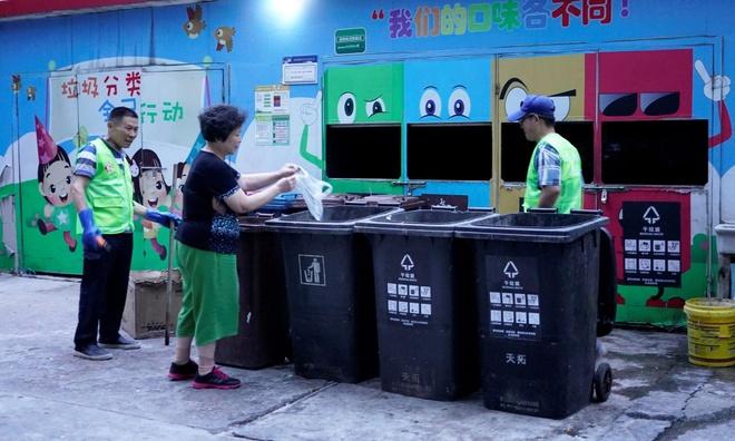 Một người phụ nữ bỏ rác vào các thùng được phân loại khác nhau tại Thượng Hải, bên cạnh là các tình nguyện viên hỗ trợ. Ảnh: Reuters.