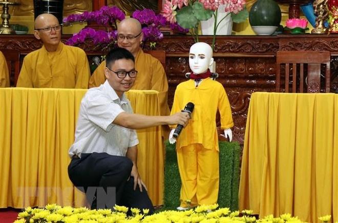 Tiến sỹ, kỹ sư Nguyễn Bá Hải hướng dẫn người dân đặt câu hỏi về Phật pháp cho chú tiểu Giác Ngộ 4.0. Ảnh: Xuân Khu/TTXVN.