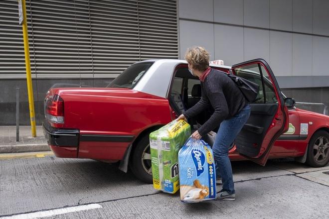 Một phụ nữ chất giấy vệ sinh và khăn giấy mới mua lên xe taxi ở Hong Kong, ngày 6/2. Ảnh: Bloomberg.