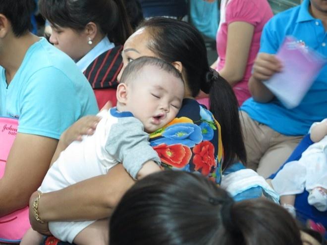 Em bé ngủ trên tay mẹ chờ đến lượt tiêm phòng. Ảnh: Khánh Trung