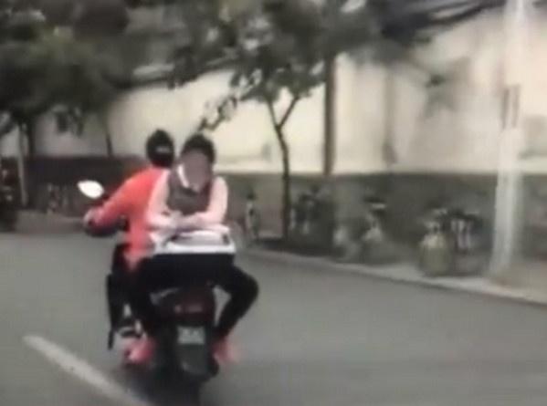 Nu sinh tranh thu lam bai tap khi ngoi nguoc sau xe may hinh anh