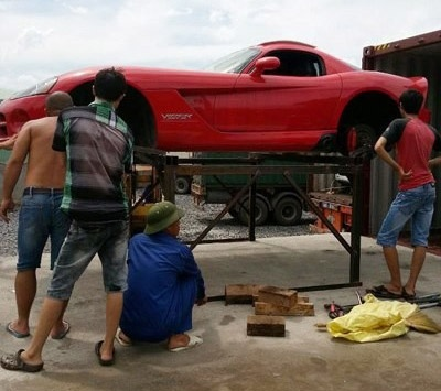 Rolls-Royce Phantom thay lop tren via he Ha Noi hinh anh 4 Chiếc xe thể thao Dodge Viper tại Quảng Ninh được kê lên một chiếc khung sắt thô sơ rồi thay lốp, khiến nhiều người ngạc nhiên. Hình ảnh này cũng được nhiều tờ báo quốc tế đăng tải lại.