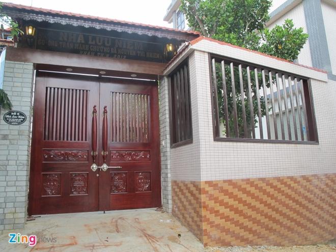 Ngoi nha doc nhat vo nhi lam tu 700 m3 go dinh huong hinh anh 1 Ngay từ lúc bước vào cổng, mọi người sẽ bị choáng bởi chiếc cổng của ngôi nhà này. Cửa cổng được làm từ hai tấm gỗ nguyên khối dày 10cm, cao 2,5m, rộng 1,2m/1tấm. Xung quanh cổng cũng được trang trí đèn màu bắt mắt. phía trên ghi dòng chữ: Nhà Lưu niệm gia đình ông Trần Quang Chưởng và bà Nguyễn Thị Nhiên.