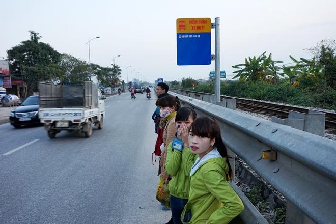 Hành khách đợi xe tại bến buýt gần khu bến xe Thường Tín phải nép sát vào rào chắn đường sắt tránh dòng phương tiện lưu thông mật độ cao.