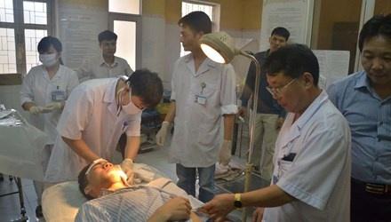 Loi ke nan nhan xe khach dam nhau tham khoc hinh anh 1 Các bác sĩ Bệnh viện Đa khoa Sơn Tây đang khâu vết thương cho nạn nhân Đỗ Bá Đồng.