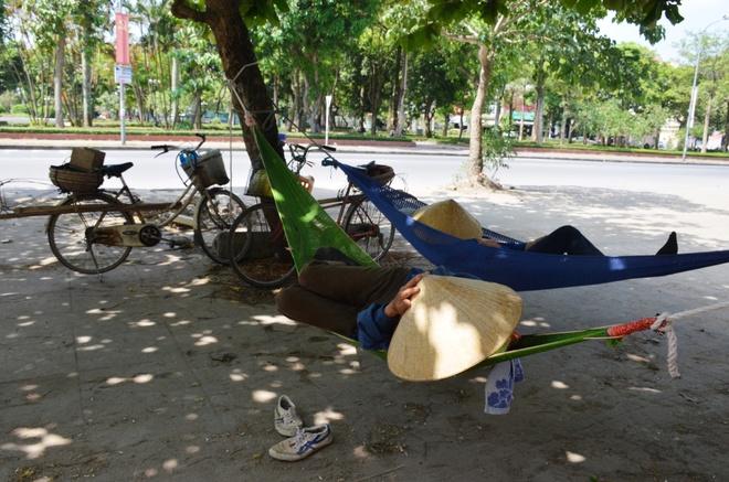 Chao lua mien Trung trong cai nong 40 do C hinh anh 4 Hình ảnh hai nữ cửu vạn đang nằm nghỉ trưa tại công viên Tam giác Quỷ, phường Quang Trung, TP Vinh. Chị Nguyễn Thị Lam (42 tuổi, ở huyện Hưng Nguyên, Nghệ An) cho hay, nắng nóng ảnh hưởng đến cuộc sống của tất cả mọi người. Chính chị và những nữ cửu vạn khác cũng ít việc hơn, buổi sáng đi làm thì phải dậy sớm vì trưa nắng chẳng có ai thuê làm cả.