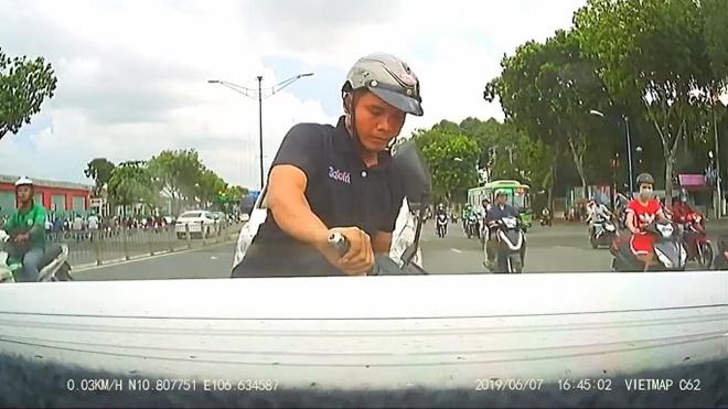 Thanh nien di xe may dam thang duoi oto vi mai bam dien thoai hinh anh