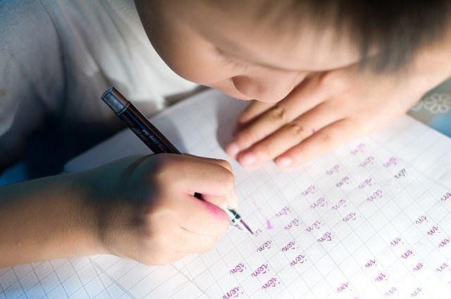 Cho con hoc chu truoc 6 tuoi, sau 25 nam con de bi dien? hinh anh 1 Ngồi sai tư thế cúi gằm xuống bàn là tư thế dễ phạm phải của trẻ học chữ sớm. Ảnh tư liệu