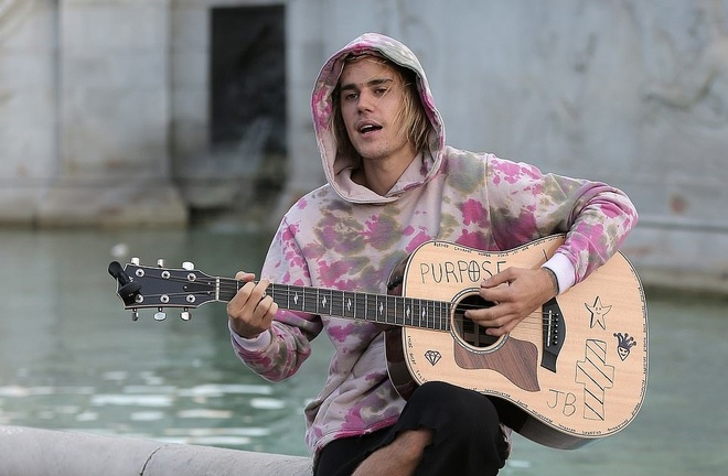 Justin Bieber vua dem dan guitar vua hat tren pho hinh anh