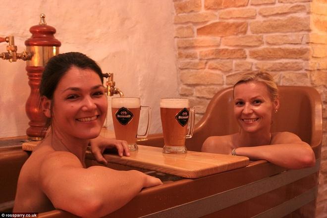 Tam bia tro thanh mot voi cac du khach den Cong hoa Sec hinh anh 1 Hai du khách nữ đang ngâm mình và uống bia ở Beer Spa tại Prague, nơi du khách có thể thỏa mãn đam mê với bia từ ngoài vào trong. Ảnh: Dailymail.