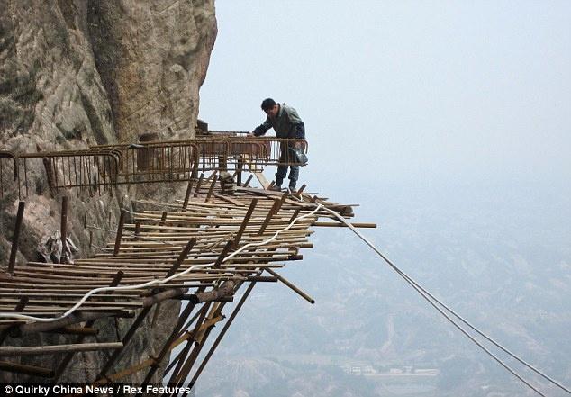 7. Đường trên trời bằng gỗ, núi Shifou, Trung Quốc: Không để tỉnh bạn qua mặt, cách đó 130km, tỉnh Hồ Nam đã xây dựng một đường trên trời bằng gỗ vô cùng độc đáo ở núi Shifou. Con đường rộng chưa đầy 1m được làm từ ván gỗ nằm ở độ cao 300m so với mặt đất, kéo dài gần 3km. Đây là đường ngắm cảnh dài nhất Trung Quốc. Ảnh: Wanderlust.co.uk