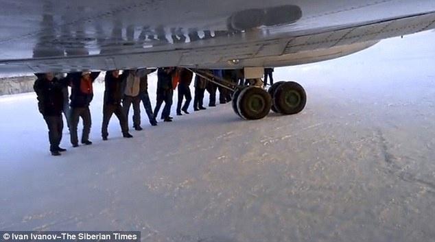Các hành khách đẩy cánh máy bay, giải phóng phanh bị đông cứng và đẩy máy bay lùi lại.