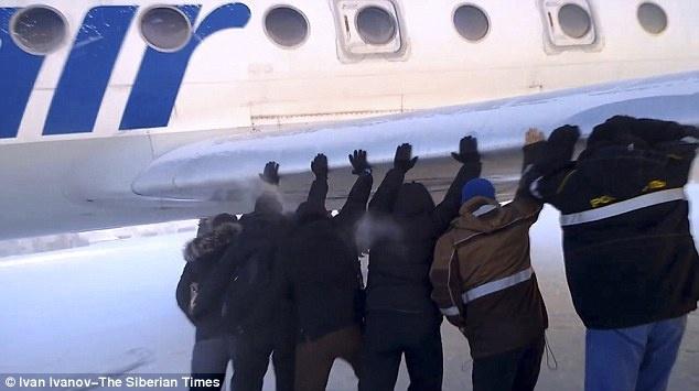 Các hành khách nỗ lực đẩy chiếc máy bay nặng 30 tấn.