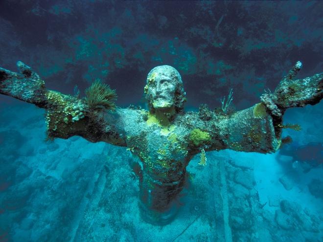 """10 diem du lich tuyet nhat hanh tinh nam duoi long bien hinh anh 1 1. Tượng Chúa Jesus dưới vực thẳm, San Fruttuoso, Ý: dù có rất nhiều phiên bản của bức tượng này nằm rải rác dưới biển, bản gốc của nó nằm ở Địa Trung Hải ngoài khơi San Fruttuoso. Bức tượng cao xấp xỉ 2,5m được tạc bởi nhà điêu khắc Guido Galletti và lắp đặt bởi thợ lặn người Ý, Duilio Marcante, vào năm 1954. Marcante  muốn đặt một đài tưởng niệm ở nơi bạn anh, Dario Gonzatti, đã qua đời vài năm trước. Do đó, bức tượng """"Chúa Jesus dưới vực thẳm"""" đã ra đời."""