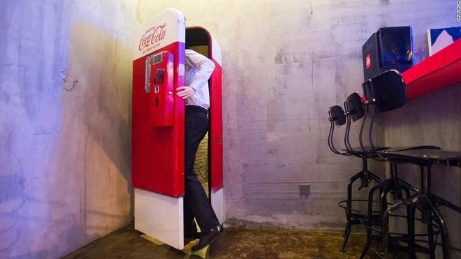 Nhung quan bar o Thuong Hai tim moi mat moi thay loi vao hinh anh 1 Flash: Nếu bạn thấy khát khi đang chu du Thượng Hải, máy bán Coca-Cola này sẽ giúp bạn giải khát theo một cách bất ngờ. Đây là lối vào bí mật của Flash, một quán bar chuyên phục vụ cocktail ở khu Tô Giới Pháp.