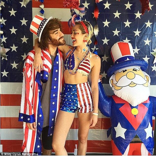 Dai gia va cac sao Hollywood lam gi trong ky nghi he? hinh anh 1 Khởi đầu mùa nghỉ lễ, Miley Cyrus tạo dáng trong bộ đồ in hình cờ Mỹ cạnh Wayne Coyne, người mặc trang phục mô phỏng Uncle Sam, vào ngày Quốc khánh Mỹ.