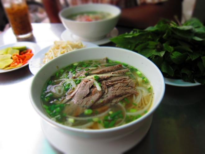 Phở, Việt Nam: Bánh phở được chan nước dùng ninh từ xương, thêm thịt gà hoặc thịt bò thái mỏng cùng rau thơm. Bạn có thể thưởng thức món ăn này ở mọi vùng của Việt Nam, với giá chỉ khoảng 1-<abbr class=