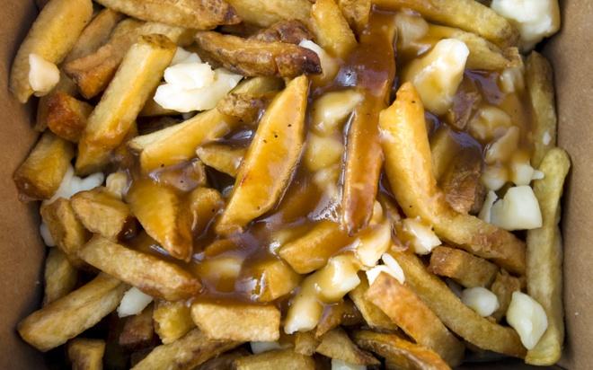 Poutine, Canada: Món ăn độc đáo này gồm khoai tây chiên rưới nước thịt và phô mai. Bạn có thể mua poutine trên hè phố với giá chưa tới <abbr class=
