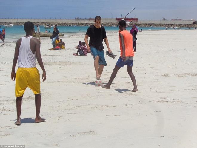 Noi du khach phai co cac tay sung ho tong hinh anh 10 Ngoài ngắm cảnh, du khách còn có cơ hội tiếp xúc với người dân địa phương. Trong ảnh, một du khách đang chơi đá bóng ở bãi biển tại Mogadishu.