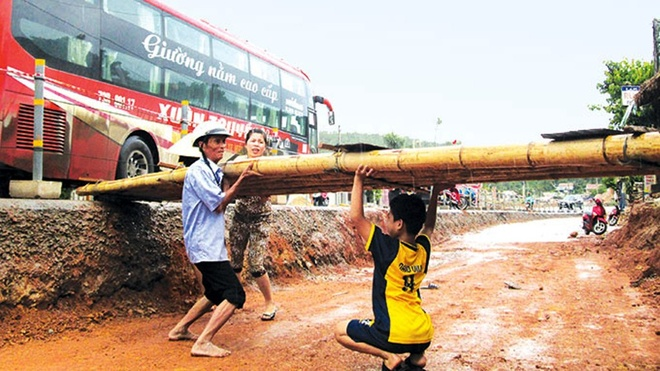 Gia đình ông Phạm Xuân Tiến (Bố Trạch, Quảng Bình) phải làm chiếc cầu tre dài hơn 4m để lấy lối đi vào nhà từ khi khởi công quốc lộ 1 cách đây cả năm trời.