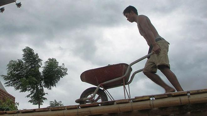 Anh Trần Tân ở phường Phú Hải (TP Đồng Hới) phải dùng xe rùa chở đá xây dựng qua cầu tạm vào nhà