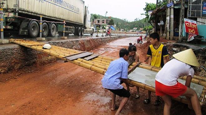 Cả nhà ông Phạm Xuân Tiến (ở Lý Hòa, xã Hải Trạch, huyện Bố Trạch, Quảng Bình) phải bắc cầu tre gần 4m ra quốc lộ 1 mới mong có khách vào mua hàng