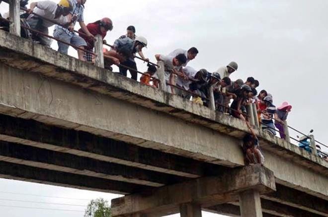 Người hiếu kỳ đứng xem chật kín trên cầu Tân Hạnh và hai bên bờ sông.