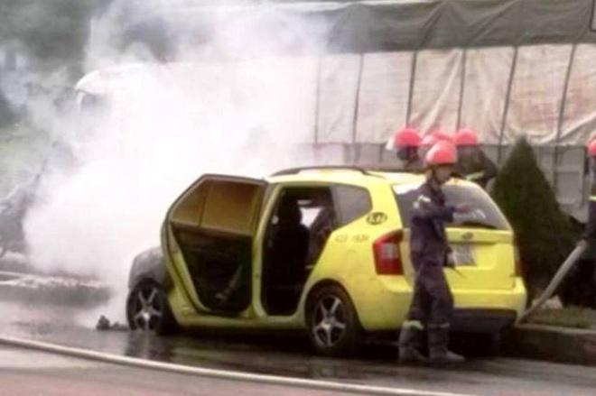 Taxi boc chay khi dang chay, tai xe dap cua thoat than hinh anh 1 Chiếc taxi gặp nạn và bốc cháy.