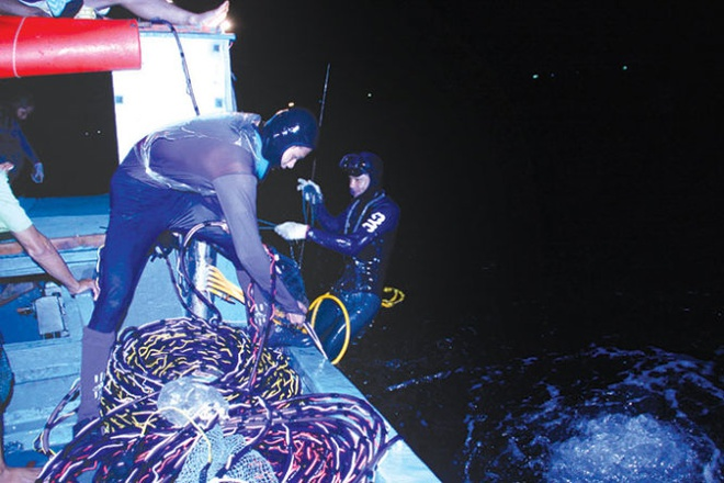 Trang dem lan bien hinh anh 1 Trước đây ngư dân trên đảo thường đánh bắt hải sản bằng lưới vào ban ngày nhưng càng ngày nguồn hải sản dần cạn kiệt, nên giờ đây họ phải đánh bắt vào ban đêm. 4g chiều hằng ngày, anh Tuấn, con trai và vài người thân trong gia đình lại mang đồ ăn lên thuyền ra biển. Chờ trời tối, họ bắt đầu mặc đồ lặn, chuẩn bị bình oxy, đèn pin lao xuống biển đi hàng giờ để tìm săn các loại hải sản dưới đáy biển. Công việc này kéo dài suốt đêm, được chia thành ba lần lặn, mỗi lần 2 - 3 giờ dưới áp lực dòng nước dưới đáy biển. Bữa cơm chiều diễn ra vào lúc nửa đêm, với bát canh đơn giản và những con cá mà họ vừa bắt được, sau đó lại tiếp tục công việc đến khi trời rạng sáng.
