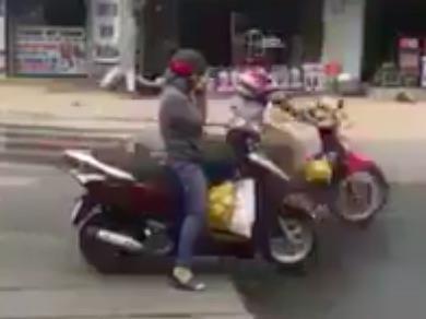 Nguoi phu nu ngoi vat cheo chan, nghe dien thoai khi dang di xe may hinh anh 2