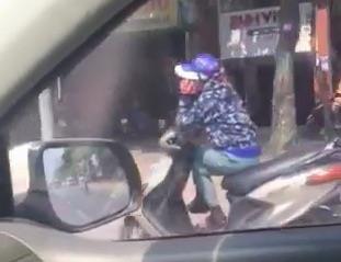 Nguoi phu nu ngoi vat cheo chan, nghe dien thoai khi dang di xe may hinh anh 1