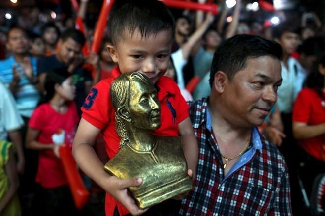 Bau cu tu do chua dem den dan chu o Myanmar hinh anh 1 Một cậu bé mang theo bức tượng bà Aung San Suu Kyi, biểu tượng cho dân chủ ở Myanmar. Bà từng bị giam lỏng tới 15 năm. Bà Suu Kyi được trao giải Nobel Hòa bình năm 1991 nhưng không thể nhận giải vì đang bị quản thúc.