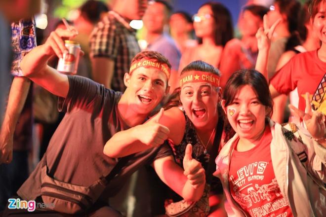 Hàng nghìn người đang hò reo mừng chiến thắng trên phố đi bộ Nguyễn Huệ. Nhiều người nước ngoài cũng đeo băng rôn cờ đỏ sao vàng, hoà cùng niềm vui chiến thắng với U22 Việt Nam.