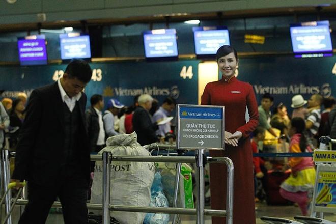 Hai hang bay 'tranh nhau' nha ga hinh anh 2 Hành khách làm thủ tục bay trong quầy thủ tục của hãng hàng không quốc gia VN Vietnam Airlines tại nhà ga hành khách T1 sân bay quốc tế Nội Bài (Hà Nội).
