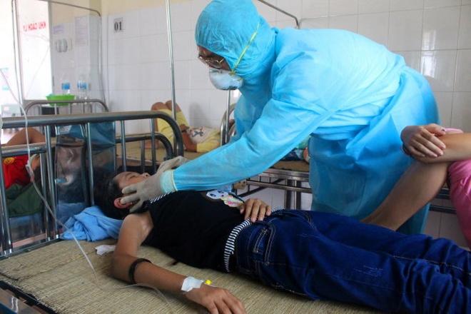 Các bác sĩ trong phòng cách ly kiểm tra nhiệt độ của các em học sinh nhập viện sáng 19-3.
