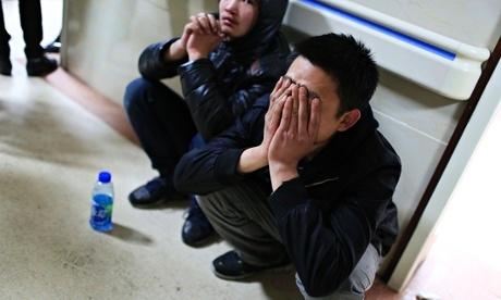Bạn của một nạn nhân trong vụ giẫm đạp ở Bến Thượng Hải ôm mặt khi chờ tin bên ngoài bệnh viện vào sáng 1/1. Ảnh: Reuters