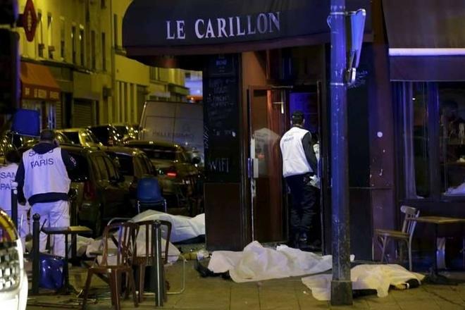 Thi thể nạn nhân được phủ kín bên ngoài nhà hàng ở Paris. Ít nhất 4 nhân viên an ninh thiệt mạng trong vụ đánh bom liều chết. Ảnh: Reuters
