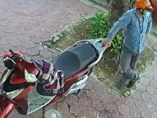 Hình ảnh một người đàn ông đeo khẩu trang đứng bên chiếc xe SH một lúc trước khi bẻ khóa.Ảnh cắt từ clip.
