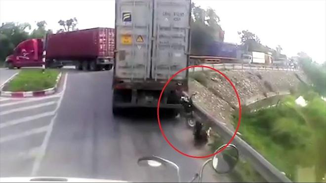 Cho den do ngay diem mu, nu tai xe bi container ep vao lan can hinh anh