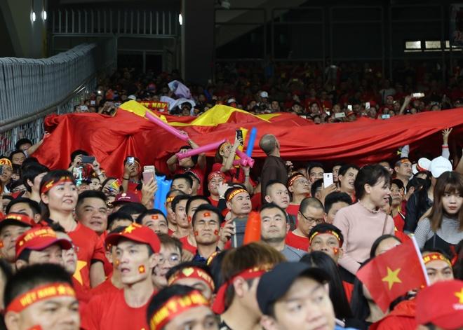 CĐV Việt Nam chuyền tay nhau cờ Tổ quốc khi các cầu thủ ra sân