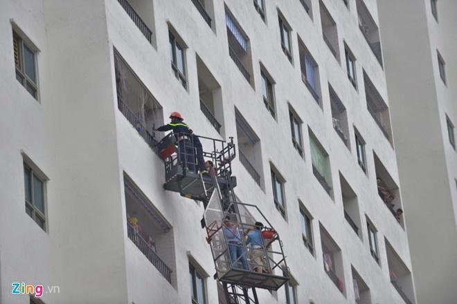 Xe thang vươn lên tầng 9 và cảnh sát cắt lưới kim loại để giải cứu người dân. Ảnh: Hoàng Anh.