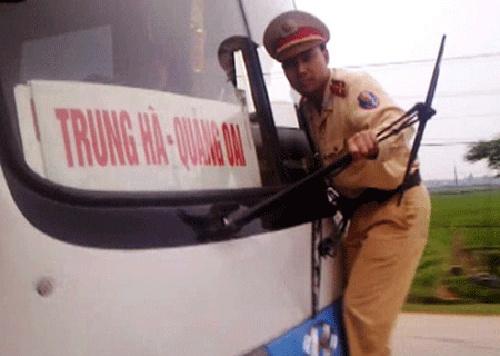 'CSGT dang nham lan giua quyen han voi quyen luc' hinh anh 2 Cảnh sát đánh đu mạo hiểm trước đầu xe khách.