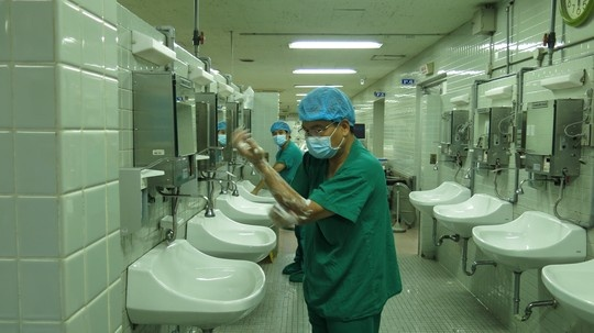 Nhung hinh anh lan dau cong bo ve ca ghep tang xuyen Viet hinh anh 1 PGS Nguyễn Hữu Ước, Trưởng Khoa Tim mạch lồng ngực BV Việt Đức, rửa tay trước khi vào cuộc phẫu thuật lấy tạng từ người cho chết não tại BV Chợ Rẫy.