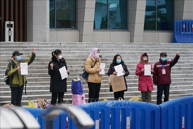 Các bệnh nhân nhiễm virus Covid-19 gây bệnh viêm đường hô hấp cấp chụp ảnh cùng các nhân viên y tế sau khi được xuất viện, tại Vũ Hán, Trung Quốc ngày 11/2. Ảnh: THX.